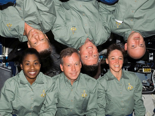 NASA portrait of the STS-121 crew in the Destiny laboratory of the International Space Station. From bottom left are mission specialist Stephanie D. Wilson; commander Steven W. Lindsey; and mission specialist Lisa M. Nowak. From top left are mission specialist Piers J. Sellers, mission specialist Michael E. Fossum, and pilot Mark E. Kelly.